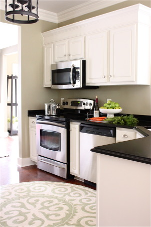 Builder Bland Kitchen Gets A Custom Look, We recently gave our builder basic kitchen a budget friendly makeover.  Using paint and trim, we made our birch, stock grade cabinets look taller.  New appliances, flooring, counters and DIY wine storage cabinet gave our kitchen a custom look.  Stop by my blog for DIY project tutorials and more dramatic room makeovers: http://www.theyellowcapecod.com, Kitchen After Makeover http:///www.theyellowcapecod.com, Kitchens Design