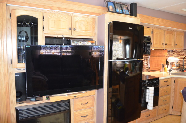RV Renovation, Completely renovated our 2003 Carriage Carri-lite. Being full timers we wanted the space to feel like our home! So when we got time off and were out of the RV for a little while we spent around 3 months changing everything out!  Some of the photos don't show the completed shades on (I made the Roman Shades myself so they took some time!) We're still planning on changing carpets in main living area and putting in a smaller version (but still bigger than the biggest RV oven) residential gas oven and a tank less water heater!  , New trim on fireplace and replaced the standard wood paneled fridge with a normal fridge, adding several cubic feet of space. Much bigger!       , Other Spaces Design
