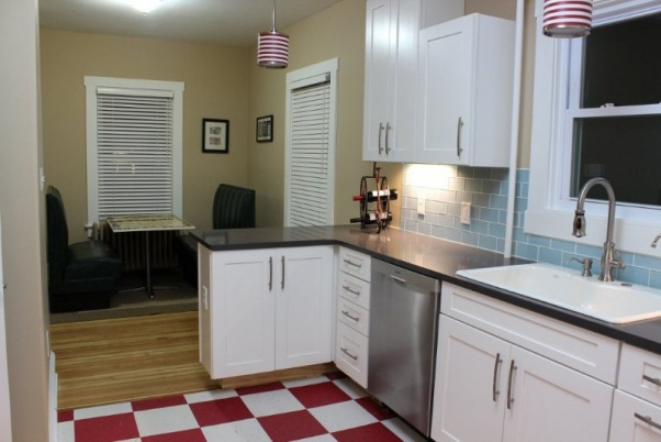 "my new kitschy kitchen, We bought an old well abused group home last year and have slowly been working our way around the first floor fixing it up on our own.  The old kitchen literally had 24"" of counter space.  By knocking out the wall between the kitchen and dining area, replacing the window with one above counter height, moving the gas and water lines, knocking out a back closet and moving the radiator we were able to create a much more functional space.  When we encountered old Asbestos tiles under the ceramic we decided not to go all the way down to the old wood, but instead cover with red/white checker board tile.  I'm in love.  , Kitchens Design"