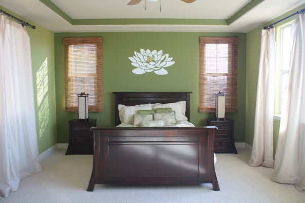 Dreamy Island Bedroom, Here's my finished master bedroom! It's got tropical influence with two shades of green, grounding wood furniture, and highlighted with cream curtains. I then decided to paint a lotus flower as a centerpiece. I used car sun reflector as my stencil, used an exacto blade to cut out the flower, then stenciled it on the wall. Took FOREVER but cost me nothing because I already had supplies and paint. I am most proud of the Lotus :) Bargain finds: bed spread Walmart, curtains Target, shades BB&B, Lowes Paint (I think we got Valspar Dune Grass & Everglade). Splurge finds: bedroom furniture Pier 1, & nara lamps Cost Plus World Market., Master bedroom day time.     , Bedrooms Design
