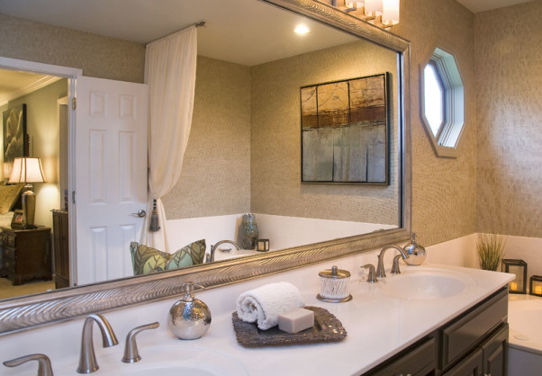"Glamour Spa Master Bath, This master bath was an outdated in an early 1990s built home. The homeowner wished for a ""spa like retreat"", but did not wish to do a complete tear out renovation. They chose to keep the existing vanity, roman tub, and large mirror as the decorator knew she could vastly update their looks! Carpeting on the floor was replaced with 18 x 18 porcelain tile, the vanity was painted an espresso, polished brass fixtures were all replaced with sleeker style, satin nickel ones. The outdated wallpaper was removed, and a soft tone-on-tone wave-like paper put in its place. The large mirror was custom framed, and the ""theater bulb light strip"" was replaced with two sleeker vanity lights. The client wanted the tub to be ""set off"" in some way, so the decorator created a soft, flowing drapery panel, attached at the ceiling and puddling on the floor. Abstract art, a ribbon shag rug, cool accessories, plus a customized vanity chair, finishes the room completely!  , Custom framed mirror in silver wave pattern, abstract art above tub     , Bathrooms Design"