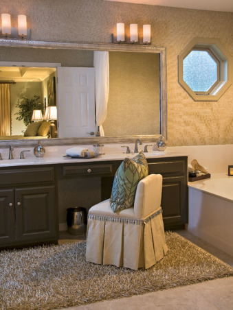 "Glamour Spa Master Bath, This master bath was an outdated in an early 1990s built home. The homeowner wished for a ""spa like retreat"", but did not wish to do a complete tear out renovation. They chose to keep the existing vanity, roman tub, and large mirror as the decorator knew she could vastly update their looks! Carpeting on the floor was replaced with 18 x 18 porcelain tile, the vanity was painted an espresso, polished brass fixtures were all replaced with sleeker style, satin nickel ones. The outdated wallpaper was removed, and a soft tone-on-tone wave-like paper put in its place. The large mirror was custom framed, and the ""theater bulb light strip"" was replaced with two sleeker vanity lights. The client wanted the tub to be ""set off"" in some way, so the decorator created a soft, flowing drapery panel, attached at the ceiling and puddling on the floor. Abstract art, a ribbon shag rug, cool accessories, plus a customized vanity chair, finishes the room completely!  , Glamour spa look without major renovation. Soothing, tranquil, tone on tone wall paper, painted vanity, custom framed mirror, customized vanity chair, ribbon shag rug to name a few changes     , Bathrooms Design"