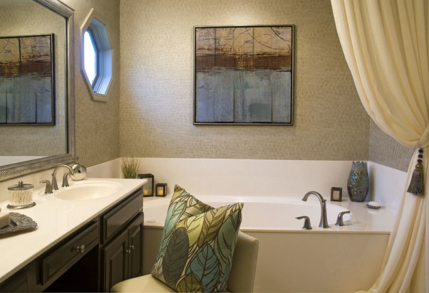 "Glamour Spa Master Bath, This master bath was an outdated in an early 1990s built home. The homeowner wished for a ""spa like retreat"", but did not wish to do a complete tear out renovation. They chose to keep the existing vanity, roman tub, and large mirror as the decorator knew she could vastly update their looks! Carpeting on the floor was replaced with 18 x 18 porcelain tile, the vanity was painted an espresso, polished brass fixtures were all replaced with sleeker style, satin nickel ones. The outdated wallpaper was removed, and a soft tone-on-tone wave-like paper put in its place. The large mirror was custom framed, and the ""theater bulb light strip"" was replaced with two sleeker vanity lights. The client wanted the tub to be ""set off"" in some way, so the decorator created a soft, flowing drapery panel, attached at the ceiling and puddling on the floor. Abstract art, a ribbon shag rug, cool accessories, plus a customized vanity chair, finishes the room completely!  , Abstract art above roman tub, new satin nickel fixtures     , Bathrooms Design"