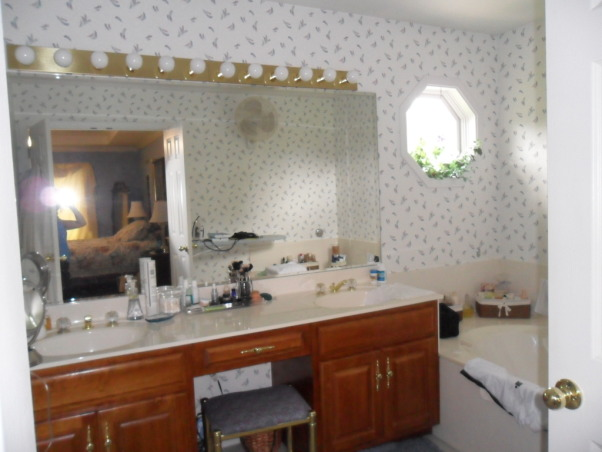 "Glamour Spa Master Bath, This master bath was an outdated in an early 1990s built home. The homeowner wished for a ""spa like retreat"", but did not wish to do a complete tear out renovation. They chose to keep the existing vanity, roman tub, and large mirror as the decorator knew she could vastly update their looks! Carpeting on the floor was replaced with 18 x 18 porcelain tile, the vanity was painted an espresso, polished brass fixtures were all replaced with sleeker style, satin nickel ones. The outdated wallpaper was removed, and a soft tone-on-tone wave-like paper put in its place. The large mirror was custom framed, and the ""theater bulb light strip"" was replaced with two sleeker vanity lights. The client wanted the tub to be ""set off"" in some way, so the decorator created a soft, flowing drapery panel, attached at the ceiling and puddling on the floor. Abstract art, a ribbon shag rug, cool accessories, plus a customized vanity chair, finishes the room completely!  , Before shot, outdated master bath vanity     , Bathrooms Design"