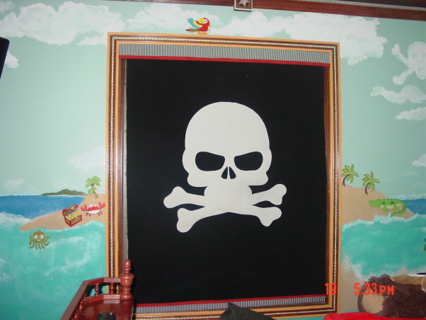 "Ahoy Matey .... From shipwreck to ship shape, Every little boy's dream bedroom starts with a theme.  My grandson wanted a ""big boy bed"" so while he was gone for the summer I designed his dream.... a pirate bedroom.  First I designed his bed which has 11 drawers and the ""12th"" is a wood pull out ""plank"" to step his way up into and out of bed.  The upper row of drawers were designed using dowels for handles which are recessed into the drawer fronts to look like little cannon portals.  The head and foot boards have a small shelf trimmed in galley railings, finials and a wood rope molding trim which runs along the upper sides of the bed and railings.    As I put grandpa to work on building the frame for the bed I got started on what was to be just a simple color on the walls.  This quickly became much more than just simple.  A mural took on a shape of it's own.  I made a ""palm tree"" using a 5 foot bamboo piece and an artificial palm frond then mounted it to the wall.  Next, little wooden pirate themed pieces and ocean creatures were then glued to the walls at varying places in the mural.    A pirate map painted on canvas I had purchased was framed on a opposing wall and coordinated with shelving I made and mounted just above the map.  On the shelving we placed small lanterns and themed items we purchased. such as a pirate book, a string of wooden fish and then mounted a cast iron bell with a ringer beside the shelving and framed map.    At the head of the bed I made a ""sail"" for the wall in layers and stuffed them for depth/dimension.  A wooden dowel became a mast and attached the sail to the wall using boat snaps.  (I made it removable in case it needs washing because of little peanut butter and jelly fingers).    A ship's wheel became a mounting for a modified lamp on the ceiling.  For crown moldings I used a baseboard on the ceiling and the walls then used rosettes in the center of the walls and decorative pieces in the corners.  The window, door and closet moldings were custom hand painted to coordinate with the colors in the room.  As a window treatment a plain white roller shade was then covered in black fabric with a large white cutout of crossbones and a skull so that it resembles a pirate flag when it is pulled down for privacy.    Carpeting was removed and in it's place I installed a wood grain floating vinyl flooring.  Then last but not least, the double closet with mirrored sliding doors was gutted and the inside was designed so that my little pirate could reach his clothing and shelving was added for books and toys as well as his other treasures (stuffed animals etc.)  Room completed and not a day goes by that my little buccaneer doesn't tell us just how much he loves his room... his own personal little tropical fantasy., Boys' Rooms Design"