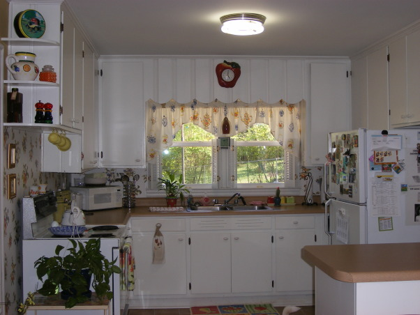 "50's Cozy Cottage Kitchen, Our kitchen space is cute, but old. The cabinets have been repainted many times. The floor is uneven because of multiple layers of linoleum. The appliances need replacing. Something is leaking between the fridge and dishwasher and we don't know which so we keep a towel underneath the fridge to soak up the water coming from somewhere. The bar/pantry is so deep, things get lost and you never see them again. The bar really isn't a bar it's a ""catch-all"" and we need more space!! , This is the cute, cozy, cottage kitchen that needs updating and more storage and space , Kitchens Design"