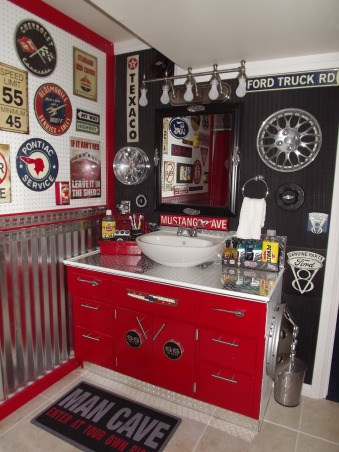"Vintage auto themed bathroom, Basement bath for my teen boys done in a garage / vintage auto theme, The ""after"" vanity. The pix really do not do it justice, it looks like a big toolbox. The back wall is made from $10 faux tire mats that are for a garage. I painted a toolbox to hold their toiletries . I have not found the right shades for the light fixture just yet. While some may think the wall is to busy and the mirror to small we actually like it that way., Bathrooms Design"