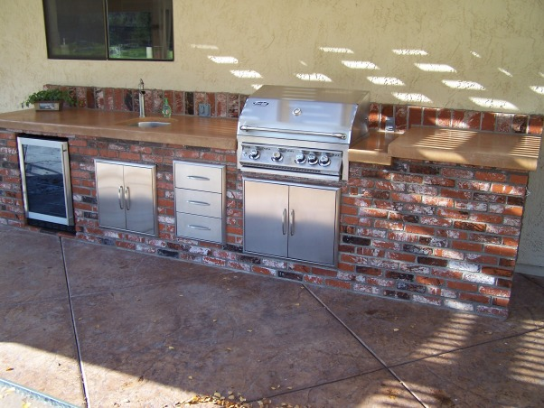 Patio makeover and out door kitchen, updated and enlarged patio with an added outdoor kitchen, After: new out door kitchen with gas grill, concrete counter top, frig, sink and storage.  The patio was enlarged with stamped concrete , Patios & Decks Design