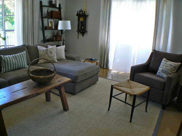 Change for the seasons, 15 x 19 Living/Family room area painted in Dove grey. Ikea sofa/sectional in grey-brown cordoroy covers, Classic slope arm chair, old wood bench/coffee table, teak end tables in separate styles, Stressless recliner. Blend of old and new . Refinished concrete floors with sisal area rug. Kids and cat friendly!, My fav stool from aunt Laurell's garage, A Regulator clock on the wall that I found in England 'back in the day.  , Living Rooms    Design