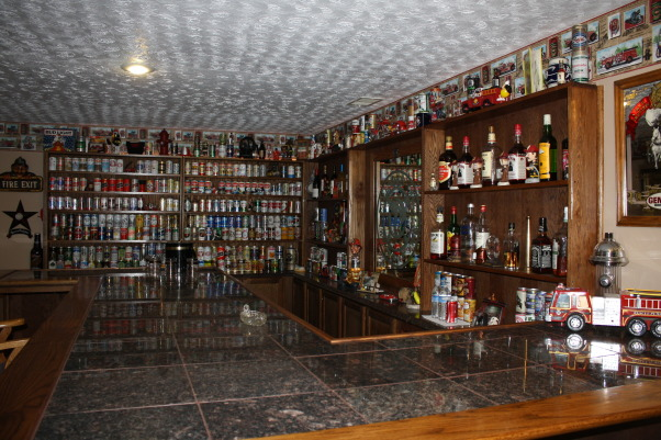Fire Fighters Man Cave, A 14' x 40' finished area that I have made into my firefighters Man Cave for entertaining guest. , With over 300 different beer cans displayed there is still room for the hard liquor and wine., Basements Design