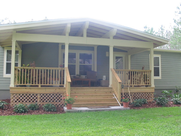 Front Porch Addition and Landscaping, One of a kind front porch addition with a craftsman style.  This Manufactured (Mobile Home) originally came with tan Vinyl Siding that kept buckling.  We replaced it with Hardi Plank and built a big, chunky front porch.  At first, the porch was overwhelming, but now that we've got the landscaping done and looked at it awhile, it's amazing.  The rails will be painted cream color and the top rail will be stained to match ceiling.  Also, deck and stairs will be stained to match ceiling.   It now looks like a cottage and the acre (at least) of cleared land we used for the yard, looks like a vacation getaway.  , Home Exterior Design