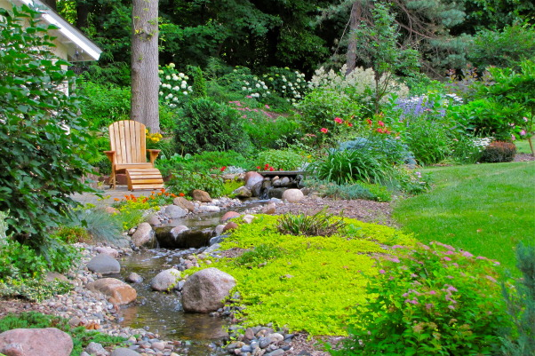 "Peace and Tranquility in our Back Yard, My husband and I transferred a 2 acre property into a combination of Country Gardens with the feel of the North Woods.  Combining many different combinations of plants:  Yellow, Green, Blue evergreens, with Roses, Weigela, Rhododendrons, Hydrandea and flowering perennials.  The tranquility of the 100ft stream we installed running down one side of the property  sets the stage ""Peace and Tranquility"" in our own Back Yard. , Yards Design"