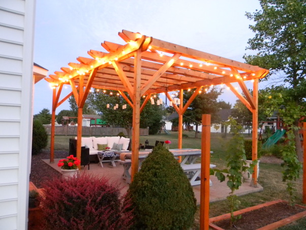 The Ultimate Honey Do: Pergola and Furnishings, Pergola with dining and entertaining space and custom touches built by my husband., A night view of the pergola.  We love the globe lights for nighttime ambiance and the candle light fixtures make the space more cozy., Patios & Decks Design