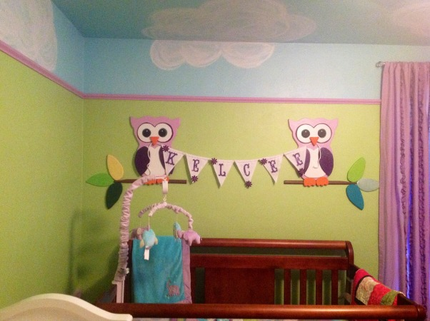 Whimsical elephant and owl nursery., Blue skies and green walls trimmed in purple with elephants and owls and a tree bookshelf., Owls displaying baby's name over the crib., Nurseries Design