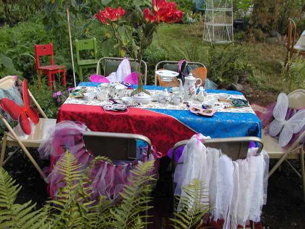 "My Little Girl Butterfly Tea Party, I had a tea party for six little girls. Ages eight to six. I wanted it in our garden so that they could be Butterflies! I wanted the lush garden plants along with the sunflowers, to give it a Wonderland appeal! I had to lower my table into the ground to be a better height for them. Then I placed rugs down around the table to help make it cozy. I found the large red flowers in a thrift store that added to my inspiration! My Daughter brought over her tulip plant and her Balcony flowers that we placed around the edges to help it feel like they were in the garden.As well as adding color in this spot.  Keeping the Butterfly theme in mind, I painted some bright flowers on a board and hand made pretty colorful butterflies so we could play ""pin the butterfly on the Flower""! This was placed on an old white door, at a height all the girls would be able to reach. The painted flowers also added a spot of color on my back wall.This back wall is the end of our very old carport. It has never been finished. It just had misc. boards nailed up. So for the party I decided to make lemonade out of my lemons by painting those boards lovely shades of tans and greens and purples! Then we hung up an old nine pane window and other out door items to finish the wall.  For added detail around the Tea table,we hung blue lights up with colorful  wind catchers to spin and catch the light.I am a fan of the primary colors so I found some lovely blue and pretty red satin fabric that i used as the table cloth. ( No finished edges i just threw it on there) Then to pull it all together I place a Teapot themed runner down the middle.  I had collected a child's china tea set in the Moss Rose design. I used it along with another rose tea pot for the girls. The Large red flower in the middle of the table set it off! I then sprinkled pink glitter over the table. At each place at the table, we placed a colorful mask, and  hand made antenna's ( I made). Then on the back of the chairs each girl received a handmade tutu ( My Daughter made) as well as the colorful butterfly wings! I did not want all the same color of wings, because this was not formal event and there are different colored butterflies in a garden! I also had the Mom's come along with a grandma or two. So naturally I had to have a table for them as well!I  It was off to the side, and blended with the butterfly theme. I think it turned out Gorgeous!  The day was Beautiful as well as Magical!, A closer look at the table. tutu's hanging, with each set of Butterfly wings Just Waiting for it's little girl!   , Gardens Design"