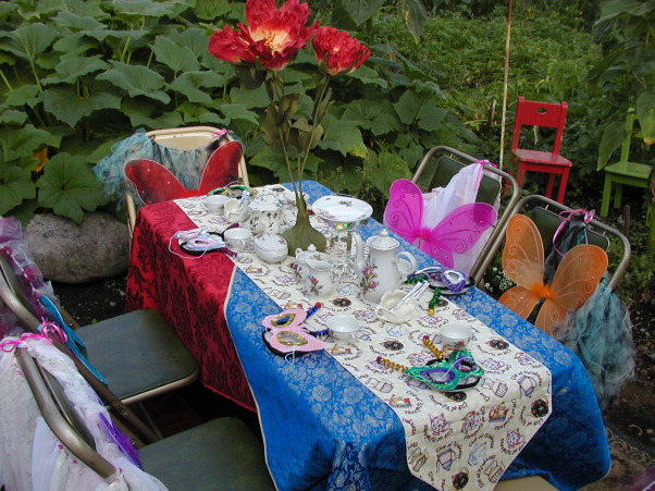 "My Little Girl Butterfly Tea Party, I had a tea party for six little girls. Ages eight to six. I wanted it in our garden so that they could be Butterflies! I wanted the lush garden plants along with the sunflowers, to give it a Wonderland appeal! I had to lower my table into the ground to be a better height for them. Then I placed rugs down around the table to help make it cozy. I found the large red flowers in a thrift store that added to my inspiration! My Daughter brought over her tulip plant and her Balcony flowers that we placed around the edges to help it feel like they were in the garden.As well as adding color in this spot.  Keeping the Butterfly theme in mind, I painted some bright flowers on a board and hand made pretty colorful butterflies so we could play ""pin the butterfly on the Flower""! This was placed on an old white door, at a height all the girls would be able to reach. The painted flowers also added a spot of color on my back wall.This back wall is the end of our very old carport. It has never been finished. It just had misc. boards nailed up. So for the party I decided to make lemonade out of my lemons by painting those boards lovely shades of tans and greens and purples! Then we hung up an old nine pane window and other out door items to finish the wall.  For added detail around the Tea table,we hung blue lights up with colorful  wind catchers to spin and catch the light.I am a fan of the primary colors so I found some lovely blue and pretty red satin fabric that i used as the table cloth. ( No finished edges i just threw it on there) Then to pull it all together I place a Teapot themed runner down the middle.  I had collected a child's china tea set in the Moss Rose design. I used it along with another rose tea pot for the girls. The Large red flower in the middle of the table set it off! I then sprinkled pink glitter over the table. At each place at the table, we placed a colorful mask, and  hand made antenna's ( I made). Then on the back of the chairs each girl received a handmade tutu ( My Daughter made) as well as the colorful butterfly wings! I did not want all the same color of wings, because this was not formal event and there are different colored butterflies in a garden! I also had the Mom's come along with a grandma or two. So naturally I had to have a table for them as well!I  It was off to the side, and blended with the butterfly theme. I think it turned out Gorgeous!  The day was Beautiful as well as Magical!, The Butterfly Garden tea Party. Using Red and Blue satin for the table cloths. Then I used a tea pot runner for the middle of the table for a bit of whimsey. Along with the large red Tulip Flower in the center for the Wonderland appeal.   , Gardens Design"