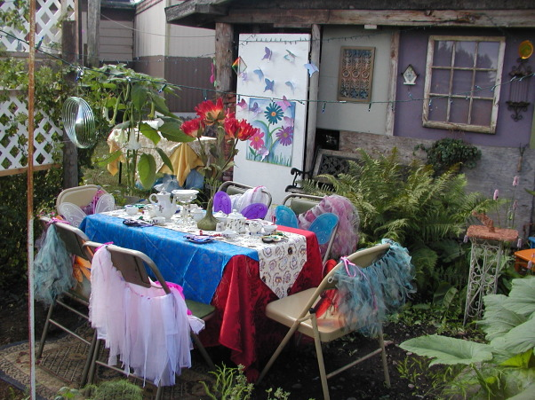 "My Little Girl Butterfly Tea Party, I had a tea party for six little girls. Ages eight to six. I wanted it in our garden so that they could be Butterflies! I wanted the lush garden plants along with the sunflowers, to give it a Wonderland appeal! I had to lower my table into the ground to be a better height for them. Then I placed rugs down around the table to help make it cozy. I found the large red flowers in a thrift store that added to my inspiration! My Daughter brought over her tulip plant and her Balcony flowers that we placed around the edges to help it feel like they were in the garden.As well as adding color in this spot.  Keeping the Butterfly theme in mind, I painted some bright flowers on a board and hand made pretty colorful butterflies so we could play ""pin the butterfly on the Flower""! This was placed on an old white door, at a height all the girls would be able to reach. The painted flowers also added a spot of color on my back wall.This back wall is the end of our very old carport. It has never been finished. It just had misc. boards nailed up. So for the party I decided to make lemonade out of my lemons by painting those boards lovely shades of tans and greens and purples! Then we hung up an old nine pane window and other out door items to finish the wall.  For added detail around the Tea table,we hung blue lights up with colorful  wind catchers to spin and catch the light.I am a fan of the primary colors so I found some lovely blue and pretty red satin fabric that i used as the table cloth. ( No finished edges i just threw it on there) Then to pull it all together I place a Teapot themed runner down the middle.  I had collected a child's china tea set in the Moss Rose design. I used it along with another rose tea pot for the girls. The Large red flower in the middle of the table set it off! I then sprinkled pink glitter over the table. At each place at the table, we placed a colorful mask, and  hand made antenna's ( I made). Then on the back of the chairs each girl received a handmade tutu ( My Daughter made) as well as the colorful butterfly wings! I did not want all the same color of wings, because this was not formal event and there are different colored butterflies in a garden! I also had the Mom's come along with a grandma or two. So naturally I had to have a table for them as well!I  It was off to the side, and blended with the butterfly theme. I think it turned out Gorgeous!  The day was Beautiful as well as Magical!, The Pin the Butterfly on the flower door shows up well here as well as part of the back wall. I Love all the colors!   , Gardens Design"
