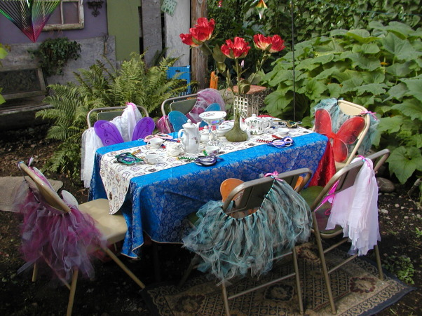 "My Little Girl Butterfly Tea Party, I had a tea party for six little girls. Ages eight to six. I wanted it in our garden so that they could be Butterflies! I wanted the lush garden plants along with the sunflowers, to give it a Wonderland appeal! I had to lower my table into the ground to be a better height for them. Then I placed rugs down around the table to help make it cozy. I found the large red flowers in a thrift store that added to my inspiration! My Daughter brought over her tulip plant and her Balcony flowers that we placed around the edges to help it feel like they were in the garden.As well as adding color in this spot.  Keeping the Butterfly theme in mind, I painted some bright flowers on a board and hand made pretty colorful butterflies so we could play ""pin the butterfly on the Flower""! This was placed on an old white door, at a height all the girls would be able to reach. The painted flowers also added a spot of color on my back wall.This back wall is the end of our very old carport. It has never been finished. It just had misc. boards nailed up. So for the party I decided to make lemonade out of my lemons by painting those boards lovely shades of tans and greens and purples! Then we hung up an old nine pane window and other out door items to finish the wall.  For added detail around the Tea table,we hung blue lights up with colorful  wind catchers to spin and catch the light.I am a fan of the primary colors so I found some lovely blue and pretty red satin fabric that i used as the table cloth. ( No finished edges i just threw it on there) Then to pull it all together I place a Teapot themed runner down the middle.  I had collected a child's china tea set in the Moss Rose design. I used it along with another rose tea pot for the girls. The Large red flower in the middle of the table set it off! I then sprinkled pink glitter over the table. At each place at the table, we placed a colorful mask, and  hand made antenna's ( I made). Then on the back of the chairs each girl received a handmade tutu ( My Daughter made) as well as the colorful butterfly wings! I did not want all the same color of wings, because this was not formal event and there are different colored butterflies in a garden! I also had the Mom's come along with a grandma or two. So naturally I had to have a table for them as well!I  It was off to the side, and blended with the butterfly theme. I think it turned out Gorgeous!  The day was Beautiful as well as Magical!, Here you can see all the colors of the table with the colorful tutu's and butterfly wings. The lush green plants around the area make it feel cozy.   , Gardens Design"
