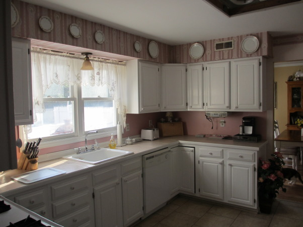 "From 90's pink to modern white kitchen, This house is 21 years old. We have lived with the pink kitchen for 12 years and finally were able to renovate it. I love white kitchens just not with  pink. The kitchen has American Woodwork  white shaker cabinets.  ""Super White"" granite countertops, white 30"" farm sink. The floor tile is 12"" x 6"" ceramic.  Stainless steel appliances. Light grey 3"" x 6"" subway tile backsplash. Breakfast bar. Desk area. Stainless steel range hood with glass., Old kitchen wall where upper cabinets were removed and wall was opened for breakfast bar      , Kitchens Design"
