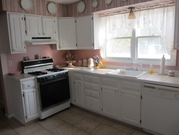 "From 90's pink to modern white kitchen, This house is 21 years old. We have lived with the pink kitchen for 12 years and finally were able to renovate it. I love white kitchens just not with  pink. The kitchen has American Woodwork  white shaker cabinets.  ""Super White"" granite countertops, white 30"" farm sink. The floor tile is 12"" x 6"" ceramic.  Stainless steel appliances. Light grey 3"" x 6"" subway tile backsplash. Breakfast bar. Desk area. Stainless steel range hood with glass., Old kitchen with pink wallpaper on soffits, pink formica  backsplash was too much pink. Soffits made the kitchen and cabinets look smaller. Double windows were removed and changed to a single slider window, which gives the illusion of a bigger window, but the opening size is the same.      , Kitchens Design"