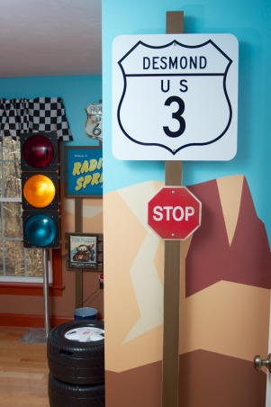 Radiator Springs, I have a three year old who is infatuated with Lightning McQueen and the world of Cars, so when we moved to a new home, I took the opportunity to create a little slice of Radiator Springs for him to live in., The entry to the bedroom has a route marker with my sons name. The mural runs all the way around the room. The streetlight in the background was an antique store find, and has been wired to operate as a real light with a red, yellow, green pattern.    , Boys' Rooms Design