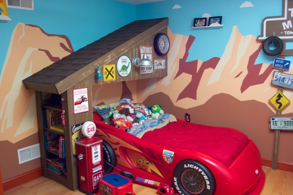 Radiator Springs, I have a three year old who is infatuated with Lightning McQueen and the world of Cars, so when we moved to a new home, I took the opportunity to create a little slice of Radiator Springs for him to live in., I designed and painted the mural, using Disney's Art of Animation hotel in Orlando for inspiration. The garage was framed by using two small shed trusses and a bookcase for the wall. The garage was then covered with rough 1x4s, painted, and shingled.     , Boys' Rooms Design