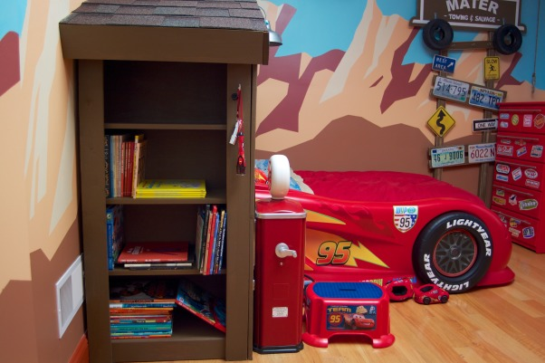 "Radiator Springs, I have a three year old who is infatuated with Lightning McQueen and the world of Cars, so when we moved to a new home, I took the opportunity to create a little slice of Radiator Springs for him to live in., The ""wall"" of the garage facade is a bookshelf.     , Boys' Rooms Design"