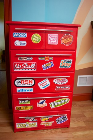 Radiator Springs, I have a three year old who is infatuated with Lightning McQueen and the world of Cars, so when we moved to a new home, I took the opportunity to create a little slice of Radiator Springs for him to live in., This Roll-away toolbox bureau was created from an unfinished piece of furniture. I removed the standard knobs and found some steel drawer pulls, painted it red, and added some logos from the Cars movie.  , Boys' Rooms Design