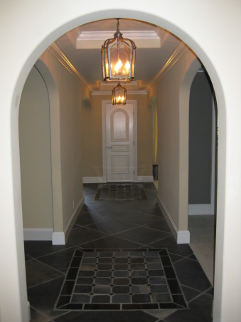 Mediterranean Entry Home Addition with before photo, My husband and I added 500 sq. feet to our home working together primarily on weekends.  This foyer space is part of the addition.  Custom iron doors open to welcome guests into an entry complete with dome ceiling and slate floors.  Traditional furnishings include a carved mirror antique Italian altarstick lamps and a hand-painted chest of drawers, The slate continues down the entry hall with stone carpets inlaid over both ceiling pop-ups.  Classic pewter iron lanterns highlight the space., Entryways & Halls