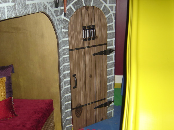 """Castle Playroom, Bedroom to playroom conversion.  Two story castle has toy storage in the """"dungeon"""" and underneath the oversized cushioned lounging area. Floor to ceiling tower is actually a climbing wall.  Castle surface is textured to give it a stone block appearance.  Upstairs is a magnetized chalk board.  Removable slide. The castle has rope lighting throughout.  Foam tiles are used for flooring.  The Cabana-style window/closet treatments have rolled-up center panels that can be closed. , Boys' Rooms Design"""