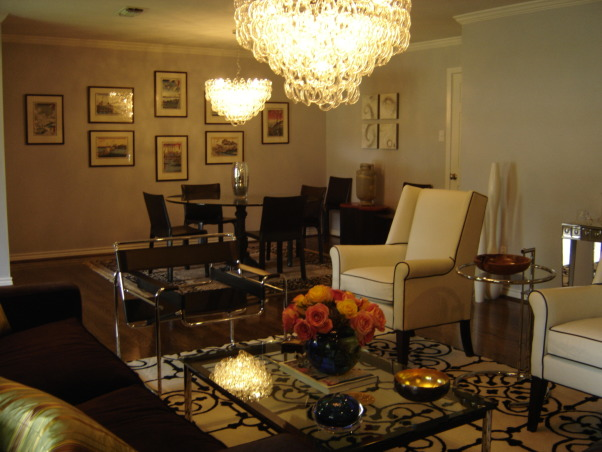 Serene Glam Dining, Romantic and elegant dining room that proves that a glamourous space doesn't have to be fussy. A soft lavender gray is on the walls to provide a serene light while the hand-blown glass chandelier adds a spark of glamour. The glass top table helps give a feeling of space while the black leather chairs and Art Deco area rug ground the space., , Dining Rooms Design