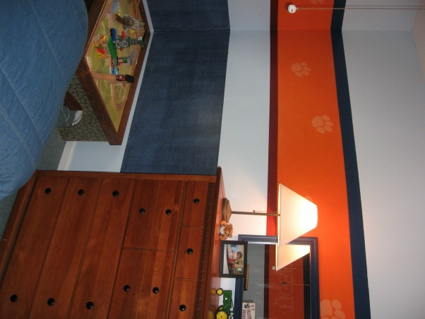 Sports / School team theme room , My 4 year old son loves sports and ClemsonUniversity.  This room is an attempt to combine both in a way that will hopefully grow with him and last until he goes to college.  Clemson's main color is bright orange However it is a small room too so I didn't want to paint the whole thing orange.  The lower navy blue band of color around the room is a denim paint technique and then I painted accent stripes of a deep red and navy.  , My son also loves trains so we added a train table., Boys' Rooms Design