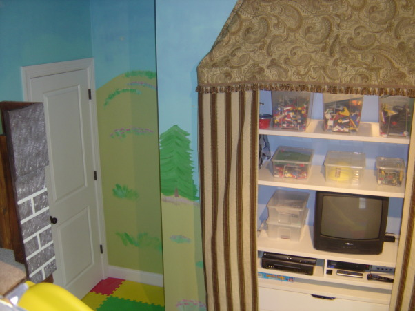 "Castle Playroom, Bedroom to playroom conversion.  Two story castle has toy storage in the ""dungeon"" and underneath the oversized cushioned lounging area. Floor to ceiling tower is actually a climbing wall.  Castle surface is textured to give it a stone block appearance.  Upstairs is a magnetized chalk board.  Removable slide. The castle has rope lighting throughout.  Foam tiles are used for flooring.  The Cabana-style window/closet treatments have rolled-up center panels that can be closed. , , Boys' Rooms Design"