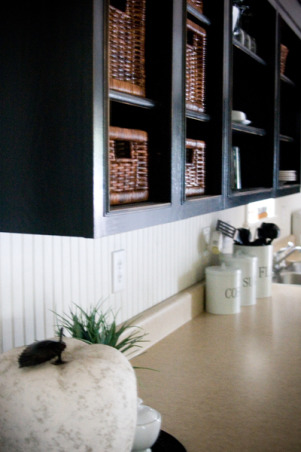 Classic Traditional Modern Kitchen with Black Cabinets, Our kitchen started out with pale green walls and the cheapest stock oak cabinetry you can buy.  We added moulding to the tops of the cabinets and painted them black. We also added a beadboard backsplash and dark chocolate laminate wood floors.  There is still plenty of work to do & stainless steel appliances to buy but here's where we are as of today!  For more photos and videos of our little fixer upper visit our website: www.TheLetteredCottage.net, www.TheLetteredCottage.net , Kitchens Design