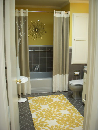 Mid-Century Yellow and Gray Bathroom, The house was built in 1956 and we moved in just under a year ago. This full bathroom is on the main living floor; there is a full master bath downstairs. All tile and fixtures are original; all we changed was the wall color and added the accessories. Before the yellow the room felt cold and cavernous. Not any more!, This photo shows the built-in cabinet (which is the color the walls were originally) and the gray toilet., Bathrooms Design