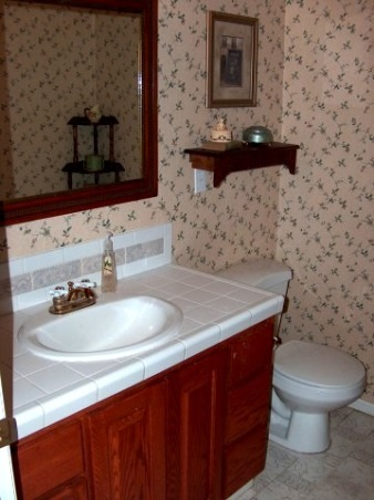 "Before and After Powder Room, This is our downstairs half bath.  Before it had wallpaper and dated finishes.  We added granite undermount sink oil rubbed bronze fixtures and travertine tile.  The flooring is 16"" travertine set on the diagonal.  The paint is divine Latte tinted just a bit darker (to add a bit of contrast from entry way)  Before the bathroom had cherry stianed oak that we re-did in a dark walnut stain.  We did all the work ourselves.  I think its complete but any suggestions?  , BEFORE.....white field tile linoleum cherry stained oak cabinets and brass fixtures.   , Bathrooms Design"