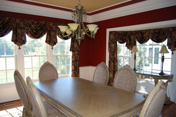 Burgundy Dining Room, This is a beautiful dining room done in red (burgundy) walls with white columns. The color scheme is brought together with a black and nuetral rug nuetral furniture and black burgundy and nuetral color window treatments. The room is accentuated with shadow boxes below the chair rail and decorative molding on the ceiling. The ceiling is also painted a complimentary nuetral color., , Dining Rooms Design