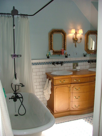 1905 Edwardian Master Bath, Our second bathroom re-do using existing second hand and overstock supplies and a lot of DIY!  This home was built in 1904 without bathrooms. Moved the plumbing around a bit and made this room into a 'period' bath for a family of four from a single-sink no-shower vinyl disaster! Total project was around $5K. All rooms will be updated but period-inspired due to the historical district trends/requirements of this neighborhood., The tub was original to the house although it had a simple chrome faucet. We added the bronze fixture with shower head and ring and bronzed the feet.  The double sink is a converted buffet from the 1930s.  Bronze wall faucets were overstock items along with the reverse-painted glass framed mirrors.  Sconce is an ebay find.  Shelves are new standard-issue at Lowes.  I tiled the bathroom myself with Olean subway and pinwheel tiles accented with craigslist-bargain glass tiles., Bathrooms Design