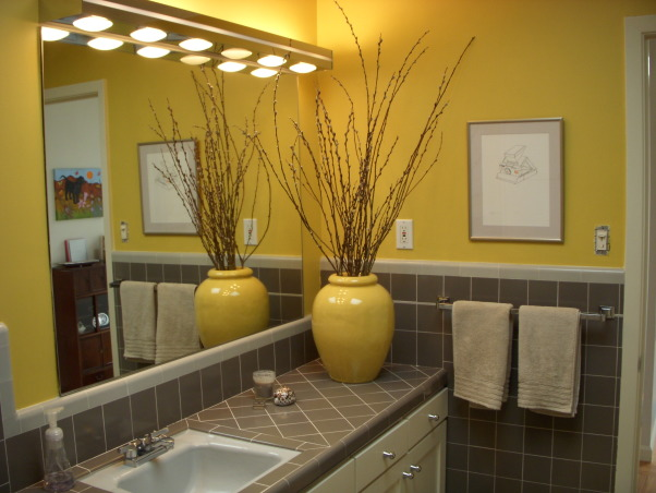"Mid-Century Yellow and Gray Bathroom, The house was built in 1956 and we moved in just under a year ago. This full bathroom is on the main living floor; there is a full master bath downstairs. All tile and fixtures are original; all we changed was the wall color and added the accessories. Before the yellow the room felt cold and cavernous. Not any more!, A few small changes here - the hand towels arrived (but the bath towels are on backorder - they are ""linen"" color from the Macy's Hotel Collection). We also framed 3 prints of Polaroid cameras with a light gray mat and thin silver frame and hung them in here - you can see one there above the towel bar. I also took the ""log"" candles out and added a gray candle (it's campfire scented - yum) and that shell was given to my husband by a village member he met while traveling in Fiji., Bathrooms"