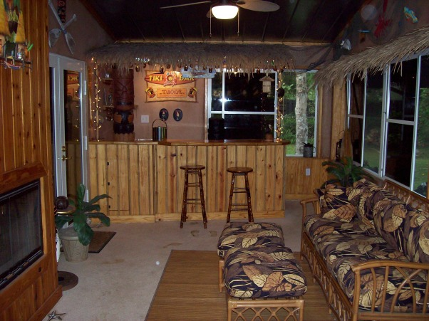 Tiki Bar, Attached 12'x26' porch on the back of our house themed as a Tiki Bar including a built in bar with a built in Beer Tap double sided fire place Faux painted floors thatch canopy over the bar and around the perimeter.  Stepping out from the porch leads onto an outdoor deck with a built in hot tub and outdoor kitchen. , View of the Tiki bar from the porch door.  Pine T&G siding surrounds the room and covers the fireplace.  Floor is Faux painted to look like a wood deck and a sandy beach.  , Porches Design
