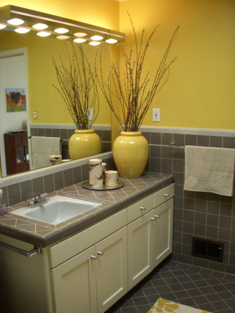 Mid-Century Yellow and Gray Bathroom, The house was built in 1956 and we moved in just under a year ago. This full bathroom is on the main living floor; there is a full master bath downstairs. All tile and fixtures are original; all we changed was the wall color and added the accessories. Before the yellow the room felt cold and cavernous. Not any more!, I rediscovered the Bauer pot (thanks Mom!) in the garage after deciding to paint the bathroom yellow and buying the area rug (Anthropologie). Added the pussywillows today because I don't have the patience for live flowers but felt the room needed some height and natural element., Bathrooms