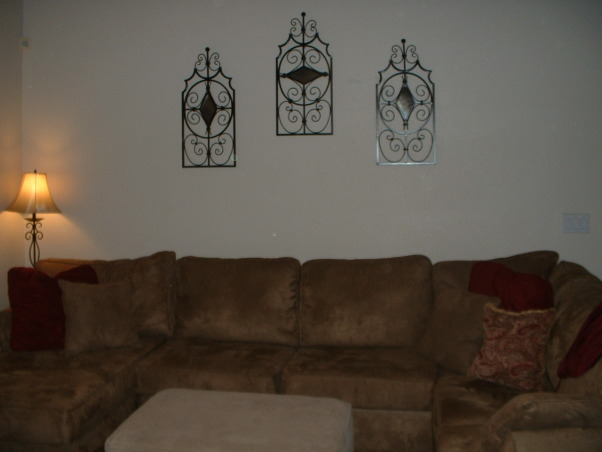 Need help decorating large blank wall in living room, I like the old world, Tuscan feel and was hoping to get some ideas as to what to do with this huge blank wall with vaulted ceiling.  Right now there are 3 metal wall art pieces, but they aren't the right scale and seem dwarfed on this huge wall.  Because of the way the room is set up, the large wall continues in to our entry way, so painting is a big chore. Maybe I could do color blocks or something? PLEASE HELP!, Living Rooms Design
