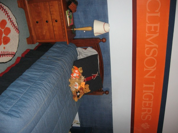"Sports / School team theme room , My 4 year old son loves sports and ClemsonUniversity.  This room is an attempt to combine both in a way that will hopefully grow with him and last until he goes to college.  Clemson's main color is bright orange However it is a small room too so I didn't want to paint the whole thing orange.  The lower navy blue band of color around the room is a denim paint technique and then I painted accent stripes of a deep red and navy.  , Someone asked where I got the stencil.  I made it by overlapping pieces of blue tape about 1/4"" onto a length of wax paper.  This gave me solid ""sheet"" to work with.  Then I layed the wax paper over the letters and tiger paw which I printed out from the computer and cut them out.  Then all you have to do is peel away the wax paper and you have a stencil. , Boys' Rooms Design"