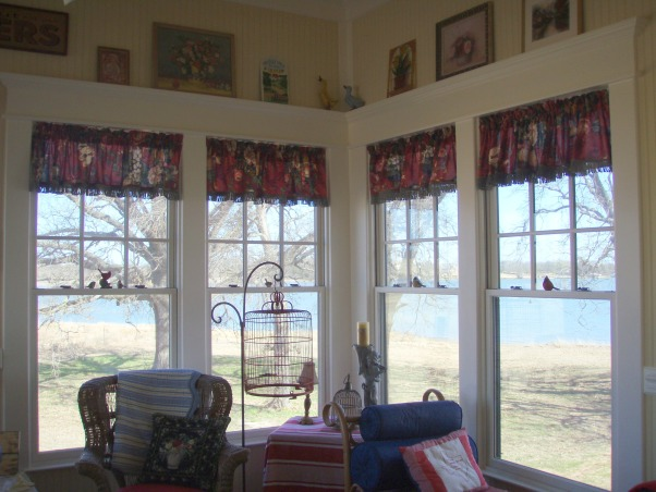 Sunroom Renovation, This is the sunroom off our Master Bedroom in the lakehouse, I added some little valances to the windows this weekend.  Salvaged more of that drapery fabric!  I made them to go just past the first pane of windows so we didn't obstruct our lake view.  And my best friend helped me rearrange the floral pictures up on top.  What do you think?, Porches Design