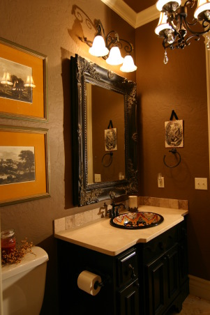 "Elegant Powder Room, We currently have this home on the market. It is located in Missouri in the Branson School District. For more information and to look at a virtual tour, the MLS number is 341835. Would make a great permanent residence or vacation home. I chose to have the powder room painted ""Sweet Georgia Brown"".  It is a small space but I wanted to use a rich color on both the walls and ceiling.  The vanity is stained black and distressed.  The sink is a talavera from Mexico.  I chose travertine for the countertops and backsplash.  The artwork came from a flea market and the colors work well with the sink.  The mirror was from a local antique store.  , View of powder room.  The crown molding really pops with the warm shade of brown on either side of it.  , Bathrooms Design"