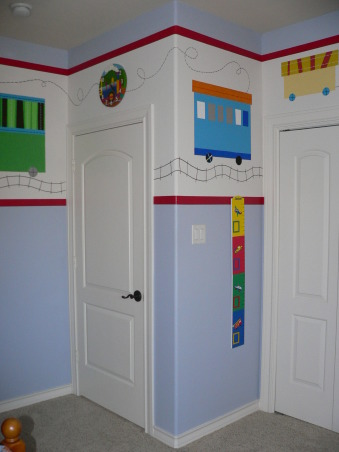 Train-Themed Toddler Boy Bedroom, My 2.5 yr old son's room was a boring tan so I decided to liven it up a bit.  The ceilings are high - 10' - so I painted a 3' high border to bring the room down to scale.  There are 23 different train cars hand-painted with acrylic paint and I added some accents in patterned scrapbook paper to enhance the design.  All of the furniture is from Pottery Barn except for the reading chair which is from Ikea.  The rug and bedspread (where I got the train inspiration) are from The Land of Nod., Boys' Rooms Design