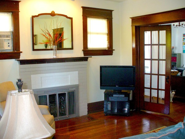 1927 Craftsman Style Bungalow HELP!, Original dark wood throughout most of the rooms except for master bedroom and kitchen in which the wood is painted white. It's hard to place furniture because there are doors everywhere in the LR. Does anyone know what the weird indent in the middle of the fireplace bricks is for?, Living Rooms Design