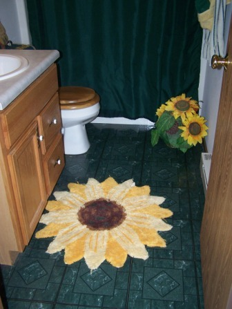 Sunflower Bathroom, This is my daughters bathroom. It is bright and cheery just like her! We stenciled ivy on the walls and then added a fake sunflower on top of it to give it dimension.  I am thinking about painting it a pale yellow this summer...what do you think?, , Bathrooms Design
