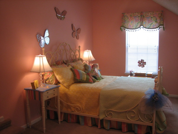 Jada's Big Girl Room, Our daughter just turned 3 so we thought it was time for her to have a big girl room. She loves this space and I am happy we were able to give it to her. It is still a work in progress but this is what we have so far. It is supposed to be butterfly themed but I still have to add some more butterfly accessories. This room is over our garage and used to be our den. We decided to move her room here so that it could double as a playroom. I will update with more pics when the I make changes, For some reason this picture came out pretty dark and really does not do the room justice. The bed skirt and paisley pillows are custom. The window treatments are custom. The butterfly mirrors over the bed came from Potterybarn kids as did the bed itself. I plan to have a large J painted and hung over the bed as well. The side tables came from my old livingroom. I had them sanded and painted for this room. The lamps came from Potterybarn kids. Lamp shades from Walmart. , Girls' Rooms Design