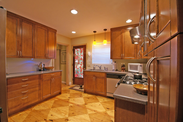 Wow Factor Floor,  kitchen was 1950's .  We added cabinets to ceiling height w/glass insert accent doors  s.s  appliances & exposed a pine sub-floor. which we scored  and stained . Added recessed lighting Corian counter  wine rack  , kitchen after showing opposite side, Kitchens Design